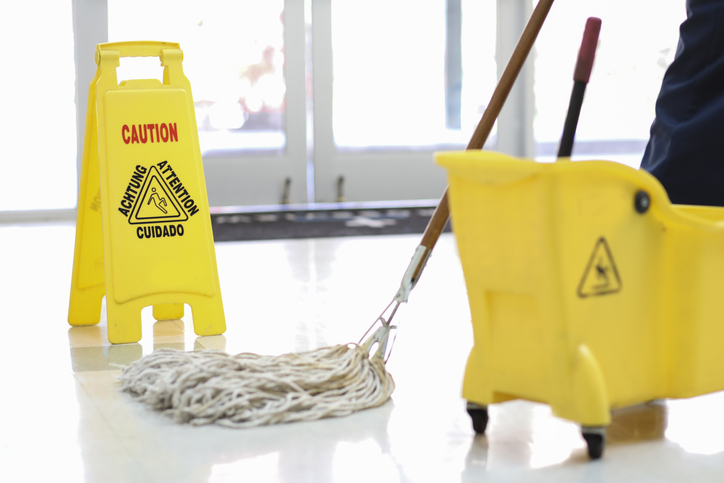 janitor using mop and bucket on floor